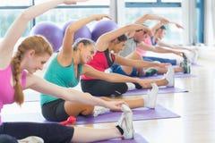 Classe ed istruttore di forma fisica che fanno allungando esercizio Immagine Stock