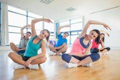 Classe ed istruttore di forma fisica che si siedono e che allungano le mani Fotografie Stock