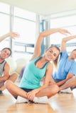 Classe ed istruttore di forma fisica che si siedono e che allungano le mani Immagini Stock