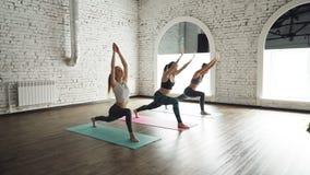 A classe fêmea da ioga está praticando a posição do guerreiro que move-se então na pose da prancha Exercícios eretos que desenvol filme