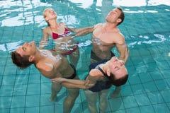 Classe felice di forma fisica che allunga nell'aerobica dell'acqua fotografia stock
