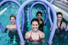 Classe feliz da aptidão que faz a ginástica aeróbica do aqua com rolos da espuma Fotografia de Stock Royalty Free