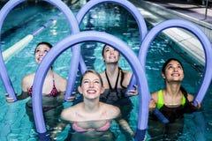 Classe feliz da aptidão que faz a ginástica aeróbica do aqua com rolos da espuma Imagens de Stock