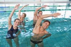 Classe heureuse de forme physique faisant l'aérobic d'aqua Photo libre de droits