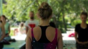 Classe mestra da ioga Agrupe a meditação no ar livre na máscara Parte traseira do ` s do professor video estoque
