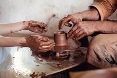 A classe mestra na modelagem da argila em um ` s do oleiro roda dentro a oficina da cerâmica imagens de stock royalty free