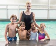 Classe mignonne de natation dans la piscine avec l'entraîneur images stock