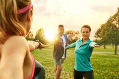 Classe mista di genere e diversa di forma fisica che si esercita al tramonto nel parco naturale Immagine Stock