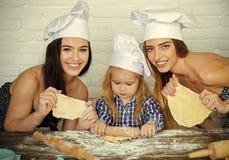 Classe principale pour la cuisson Enfant et femmes roulant la pâte sur la table Images stock