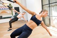 Classe que faz exercícios da tração do poder de Trx em um gym foto de stock royalty free