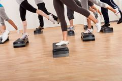 Classe que faz a ginástica aeróbica que equilibra em placas Fotografia de Stock Royalty Free
