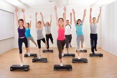 Classe que faz a ginástica aeróbica que equilibra em placas Imagem de Stock Royalty Free
