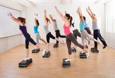 Classe que faz a ginástica aeróbica que equilibra em placas Imagens de Stock