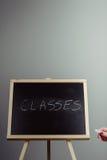 Classes écrites dans la craie blanche sur un tableau noir Images libres de droits