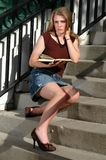 Between Classes. A pretty girl reading a book on the campus stairs between classes stock photo