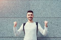 Classes canceled. Happy arabian student outside. Successful and confident young man raised hands. Celebrating achieved goal. Winner concept royalty free stock images