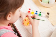 The girl paints the egg at the table at home. Classes with children in preparation for Easter. Children`s creativity. Copy space text Royalty Free Stock Images