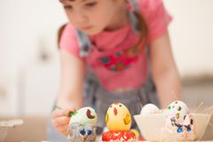 The girl paints the egg at the table at home. Classes with children in preparation for Easter. Children`s creativity. Copy space text Royalty Free Stock Photo