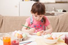 The girl paints the egg at the table at home. Classes with children in preparation for Easter. Children`s creativity. Copy space text Royalty Free Stock Photos