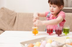 The girl throws paint in the Cup for dyeing eggs Royalty Free Stock Image