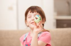 The girl holds a decorated egg and smiles. Classes with children in preparation for Easter. Children`s creativity. Copy space text Royalty Free Stock Photography