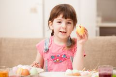 The girl holds a decorated egg and smiles. Classes with children in preparation for Easter. Children`s creativity. Copy space text Stock Images