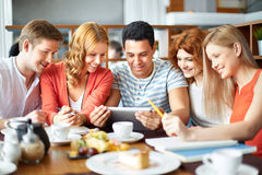 After classes. College friends sitting in cafe with touchpad after classes stock photography