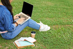 After classes. College girl sitting on the grass and using laptop after classes stock images