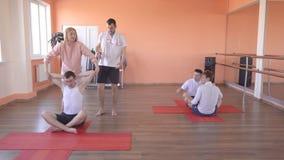 Classes de yoga avec un instructeur individuel avec une belle fille caucasienne à un centre de fitness moderne, amis masculins banque de vidéos