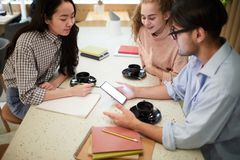After classes. Three teenagers having coffee in college cafe and chatting in social network after classes stock photography