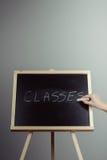 Classes written in white chalk on a black chalkboard Stock Image