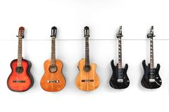 5 Guitars hanging in front of a white wall royalty free stock photography