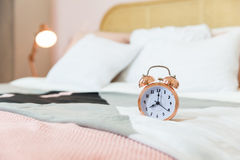 Classic alarm clock on bed. Pink classic alarm clock on bed at eight o'clock Stock Image