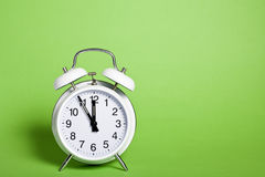 Classic alarm clock on green background. Classic white double bell alarm clock showing five minutes to noon standing on green background Royalty Free Stock Photography