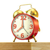 Classic alarm clock with red body and golden bells, on a table. Classic alarm clock with red body and golden bells, on a wood table and white background, close Royalty Free Stock Image