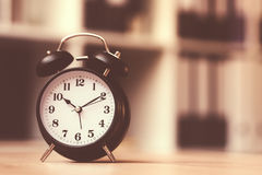 Classic alarm clock showing time during working hours in office. Classic alarm clock showing time during working hours or work break in business office, retro Stock Image