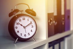 Classic alarm clock showing time during working hours in office. Classic alarm clock showing time during working hours or work break in business office Stock Image