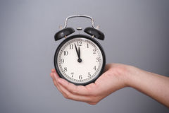Classic alarm clock in woman hand against grey background Royalty Free Stock Photos