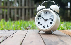Classic alarm clock on wood against nature background Royalty Free Stock Images