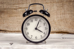 Classic alarm clock on a wooden table Stock Image