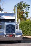 Classic American Big rig semi truck tractor with chrome details. And high chrome exhaust pipes standing on truck stop with green trees waiting for loads Stock Photography