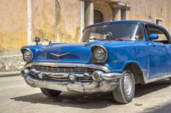 Classic american blue car in Havana, Cuba. Front detail of a classic american car passing in front of a convent in Old Havana royalty free stock image