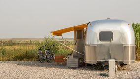 Classic american caravan. A classic chrome American trailer or caravan standing on a campingsite with two bikes and a meadow in the bakcground Royalty Free Stock Images