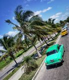 Classic American cars on road in Havana, Cuba. Classic American cars driving on road in Havana, Cuba Royalty Free Stock Photo