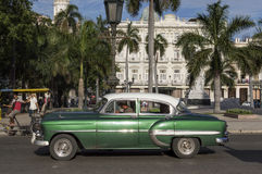 Classic american green car in Havana, Cuba. An old american car parked passing in Parque Central, Havana, cuba royalty free stock image