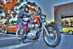 Classic American Harley Davidson motorcycle and rider. Classic American built red and black Harley Davidson motorcycle and rider at a car show in Melbourne stock photo