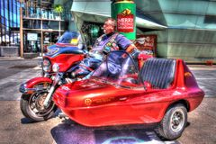 Classic American Harley Davidson motorcycle and sidecar with rider. Classic red and black American Harley Davidson motorcycle and sidecar with rider royalty free stock photography