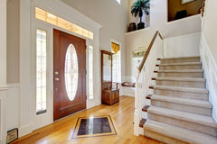 Classic AMerican home entrance interior with staircase. Classic AMerican home entrance interior with staircase and wood front door Stock Photos