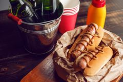 Classic American hot dogs with mustard. next to fried bacon and a bottle of beer.  royalty free stock photo