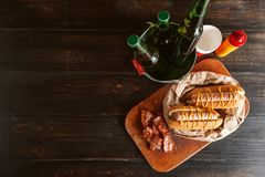 Classic American hot dogs with mustard. next to fried bacon and a bottle of beer.  stock photography